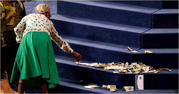 Church member offering money at a 'Health and Wealth'/'Prosperity Gospel' service.